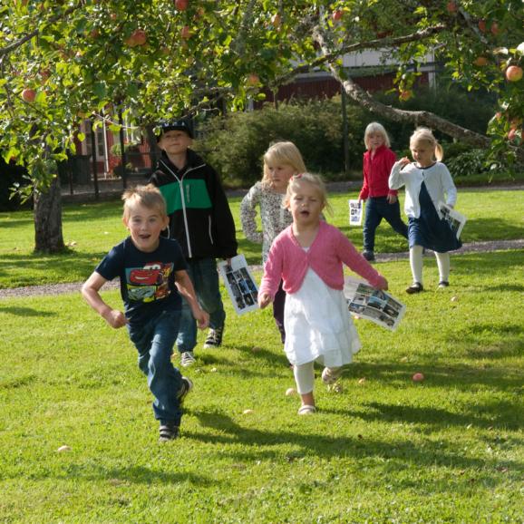 Springande barn bland äppeträd