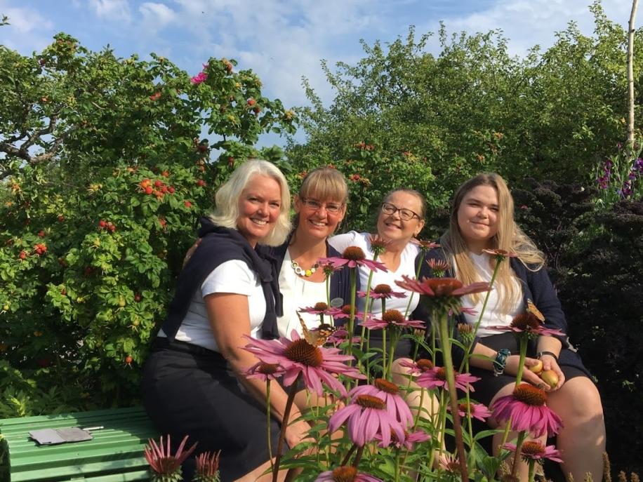Fyra kvinnor sittande på bänk i trädgård
